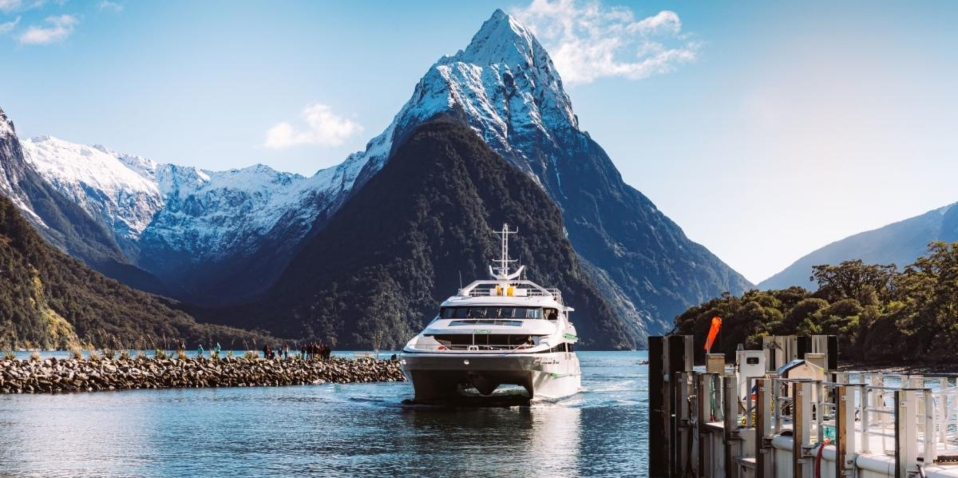 Boat cruise sailing through Milford Sound with Mitre Peak in the background