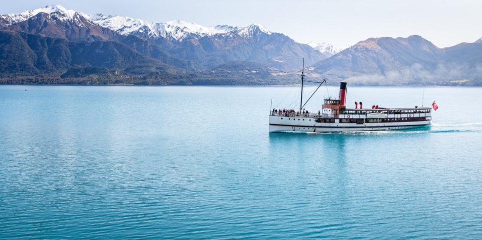 The TSS Earnslaw cruising along Lake Wakatipu with The Remarkables mountains in the background